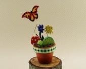 miniature painted terracotta pot with wooden turtle, butterfly, toadstool,flowers, miniature garden