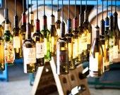 30 Wine Bottle Light Chandelier hanging from wood riddling rack