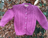 Girl's toddler handknitted pink aran cable cardigan / sweater with front buttons.