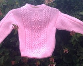 Girl's childs toddlers handknit pale pink aran cable sweater with back opening.