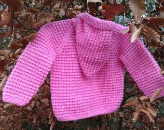Little girl's toddlers childs hand knitted bright pink jacket, coat, hoodie, cardigan with a pixie hood.