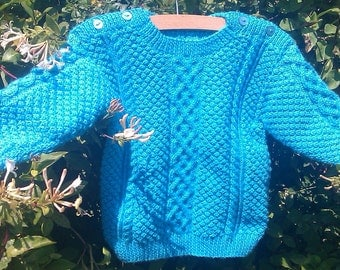 Child's Toddler's Girl's Boy's handknit azure / bright blue aran cable sweater jumper with shoulder openings.