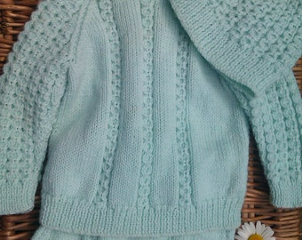 Little boy's pale green hand knitted pram suit outfit of sweater, pants and beanie hat.