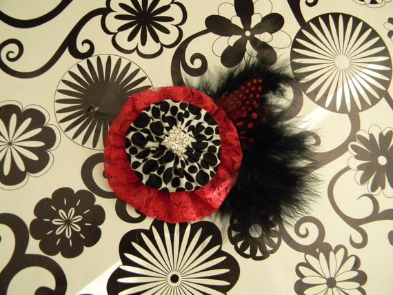 Elegant yet fun yo yo flower. red lace and black with white polka dots, with feathers. rhinestone center. Perfect for the holidays.
