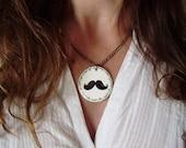 Medallón con cadena metálica con un bigote pintado a mano . Es posible personalizarlo detrás. Pieza unica.