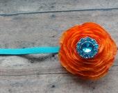 Orange ranunculus on turquoise headband with rhinestone button