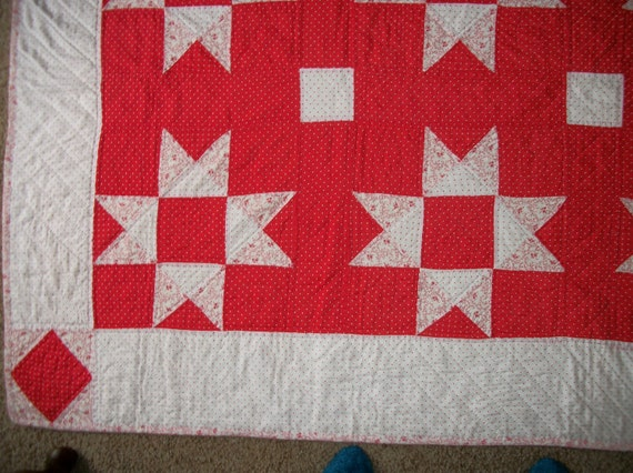 Red and white quilt with matching throw-pillow covers, beautifully hand quilted.