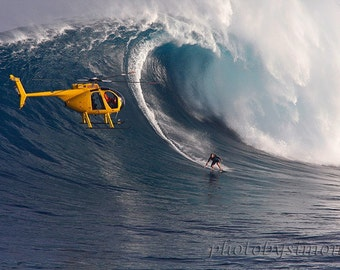 Jaws Maui a monster wave at Peahi surfer riding large wave yellow helicopter