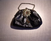 Black leatherette altered bag. Large brass flower and chain handle.