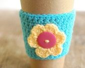 Aqua coffee cup cozy with yellow flower by  The Cozy Project
