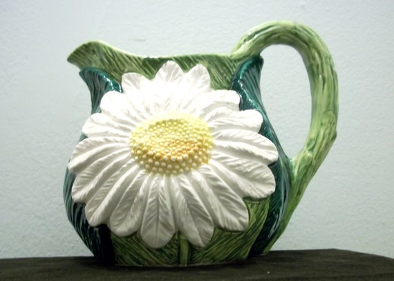 Meduim size decorative ceramic pitcher.  Green leaves and large daisies.