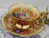 Aynsley Tea Cup and Saucer, Gilt Exterior with Hand Painted Fruit, signed D. Jones