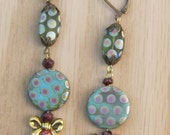 Dangle Earrings of spotted Peacock Czech coin beads in Caribbean green, garnets and antiqued brass bead caps and bows.