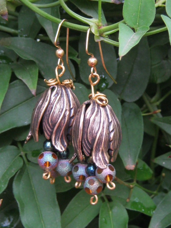 Dangling Earrings of Oxidized Brass upside down tulip shaped leaves with earth tone irredescent beads  within and gold colored ear wires.
