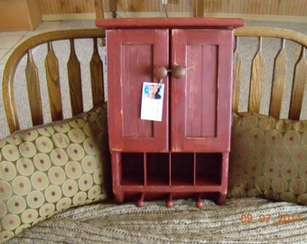 Barn red antiqued wall cabinet with double doors and pegs