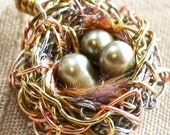 Woven wire bird nest necklace with three champagne pearls nestled on a cozy bed of jewel tone down-like nesting yarn.