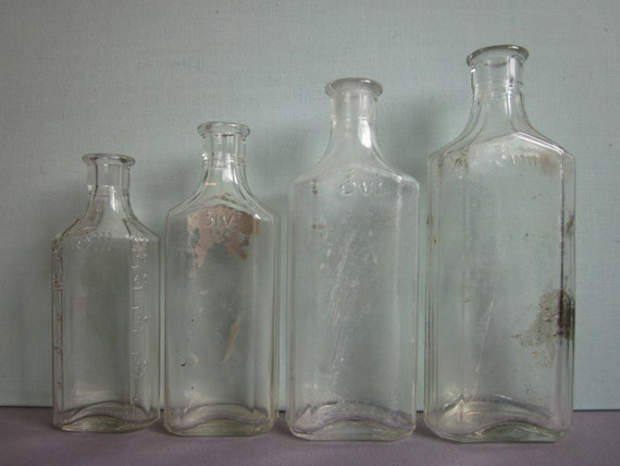 Four vintage clear glass Owens apothecary bottles in graduated sizes