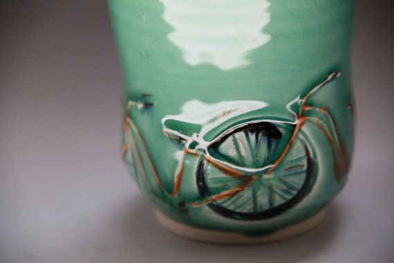 Tandem Orange Bikes on a glossy green glazed tumbler-cup: 12oz