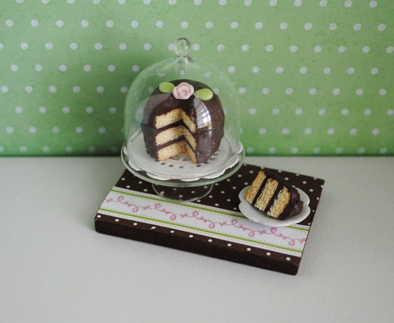 Miniature Cake With Chocolate Icing On A Covered Glass Cake