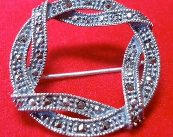 Vintage Sterling silver and Marcasite brooch.  Circular, wrapped ribbon design, safety catch. TROVAN12.1-17.3