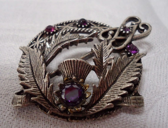 Vintage Scottish shawl pin.   Features a thistle with purple inset crystals.  UK/P-Gl.8