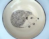 Wheel thrown shallow bowl / plate / dish with sgraffito'd hedgehog using white slip on dark chocolate stoneware