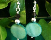 Lightweight dangles circular aquamarine colored bead with silver and black accent beads