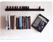 Custom made wooden book rack / bookshelf in Wenge. The pins also work as bookmarks.