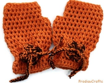 Hand-made crocheted fingerless mittens decorated with crochet flower, orange