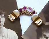 Cloak clasp or sweater guard, brass with pink gems.