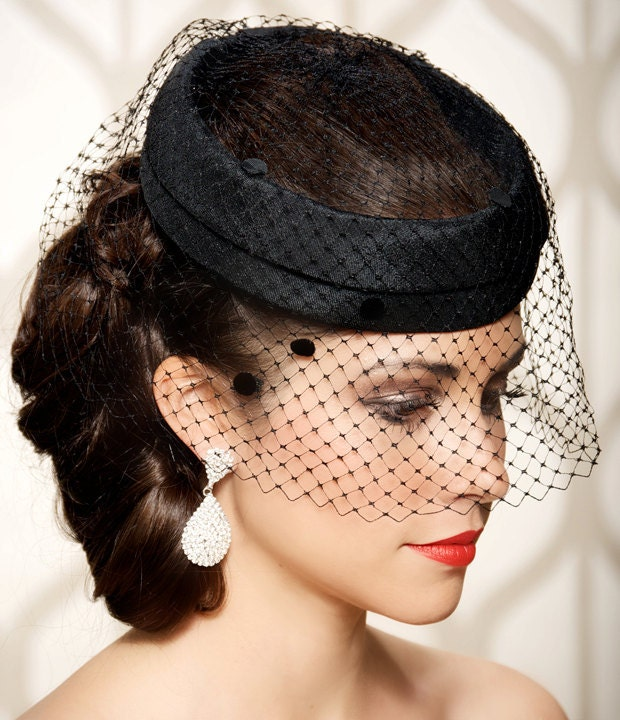 This Black Hat with Veil combines class with sass! Feathers, fishnet, and gemstone are luxurious touches to this classic black fascinator hat with an attached veil.