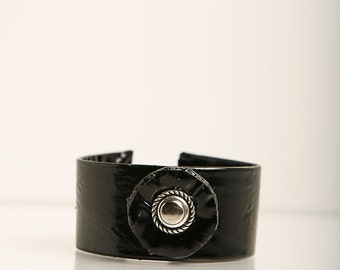 Shiny leather wristband.