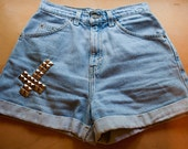 High waisted jean shorts with a studded cross on the front, right pocket.