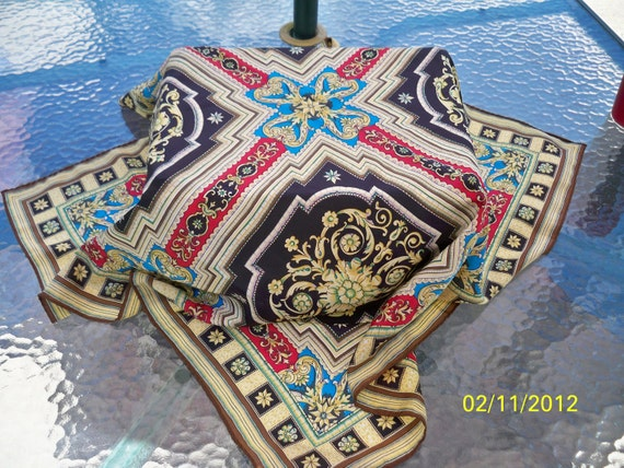 Ladies silk scarf with 4 squares that are black with gold and green design  divided by strips of red a with blue design