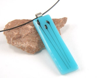 Turquoise blue fused glass necklace with black cattail floral pattern