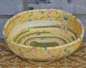 Fabric coiled oval mostly yellow basket with bear accessory