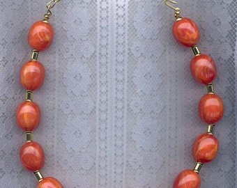 Lucite orange bead necklace. Circa 1970s.