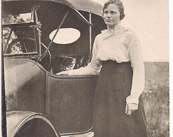 Vintage/Antique  photo of a woman in a dress standing next to a vintage car