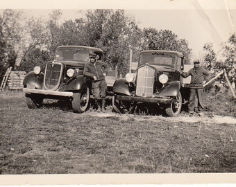 Vintage/Antique photo of 2 men standing beside their vintage trucks
