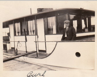 Vintage/Antique photo of a man and a fancy boat