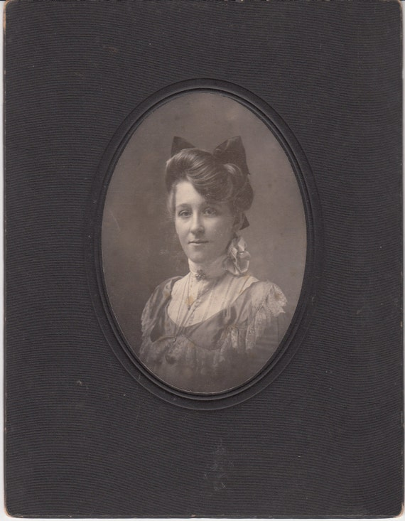 Vintage/Antique cabinet photo of a woman in a satin dress with a big hair