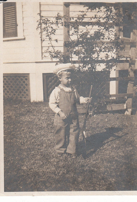 Vintage/Antique photo of  a cute boy in a coveralls holding a toy gun