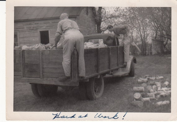 Vintage/Antique photo of two men unloading a pile of fire wood from the truck