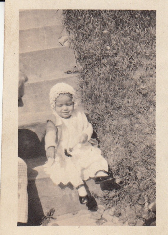 Vintage/ Antique photo of a cute baby in a dress and bonnet