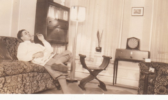 Vintage/Antique photo of a man lounging on a sofa smoking a pipe