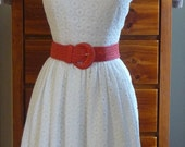 White cotton lace dress, features fitted bodice and full skirt.