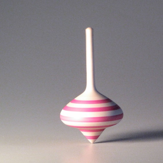 Toy spinning top with pink stripes