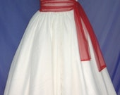 A stunning one-strap 50s style cocktail dress with a beautiful waist defining red sash.