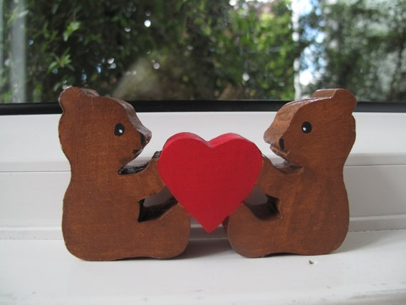Small wooden bears holding a red heart