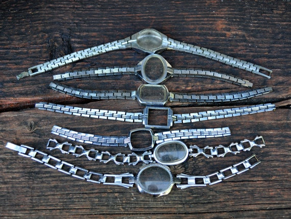 Lot of 7 vintage small watch cases with metal strap.